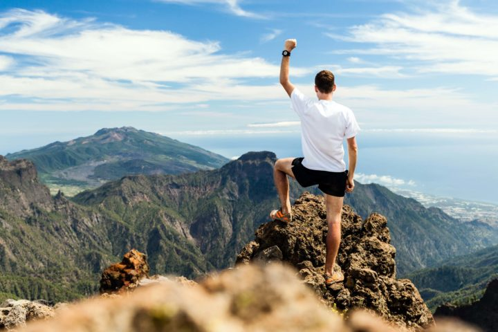 Man triumphantly at the top of a mountain